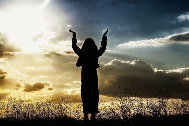 woman praying to the sun