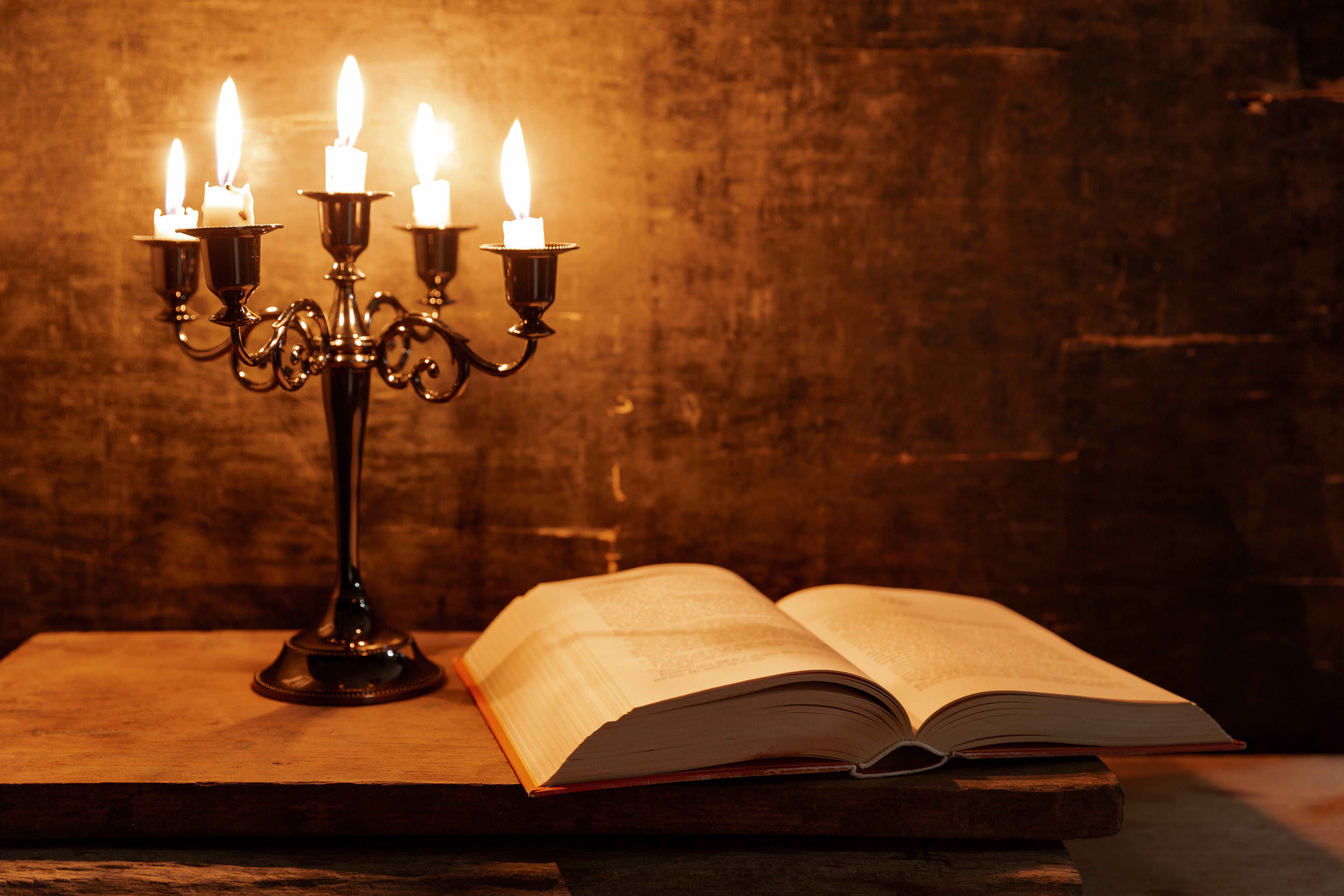 Open Holy Bible and candle on a old oak wooden table