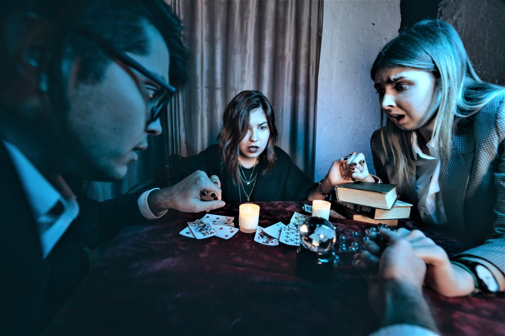 People hold hands of night at table with candles to conduct a seance to hear and talk to the dead.